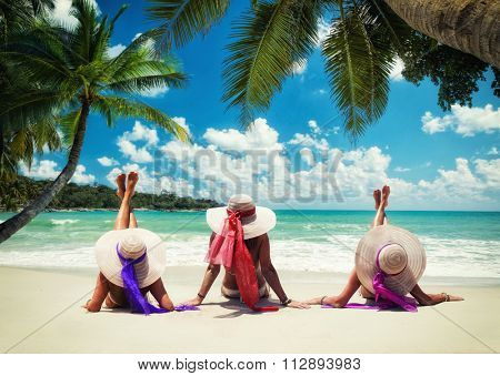 Three women in white swimsuit on the beach under the coconut tree