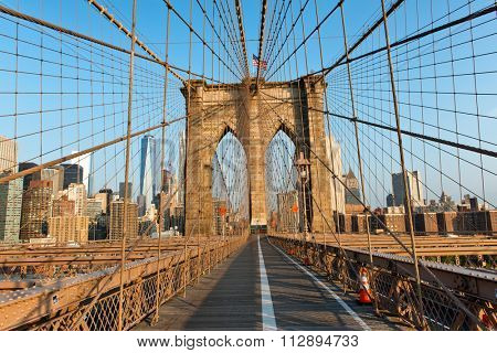 New York City viewed against the skyline from the pedestrian walkway on Brooklyn Bridge with a tower and the steel cables in the foreground in warm light