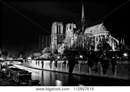 Black And White Notre Dame Cathedral At Night Over The River Seine In Paris, France.