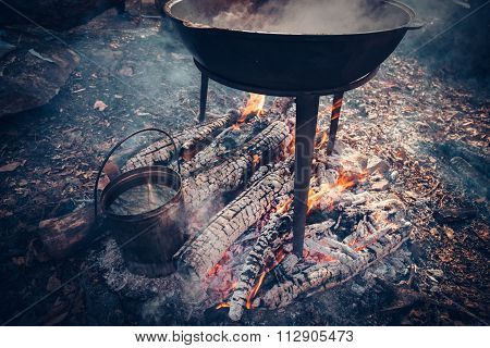 Large Pot Over A Campfire Cooking In Cast-iron Cauldron In Nature.