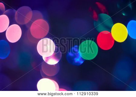 Christmas lights defocused background. Vintage styled holiday abstract bokeh in  pink, red and green