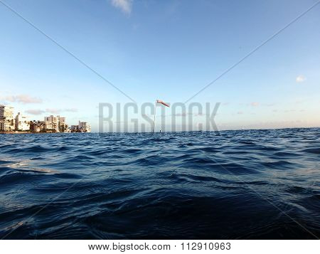 Flag Pole With Wind Sock Rises Above The Wavy Water