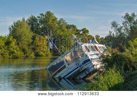 Arles, France - September 8, 2015: A sunken wooden boat in a river in France