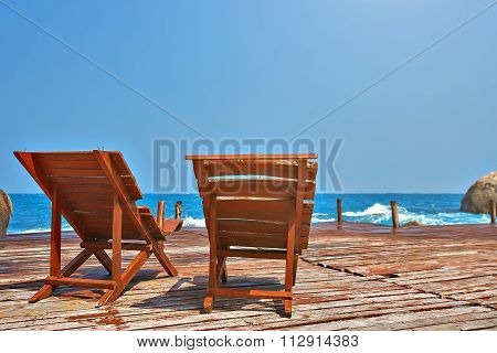 Sun beds on a wooden bridge in the sea