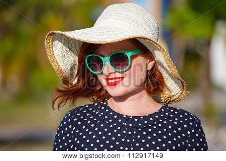 Young woman in polka-dot dress and straw hat