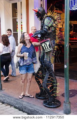 Street performer dressed as a monster and photographed for tips