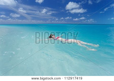 Woman floating on a back in the beautiful sea