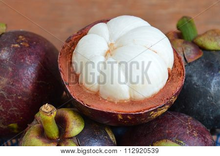 mangosteen tropical fruit peel out on wood table