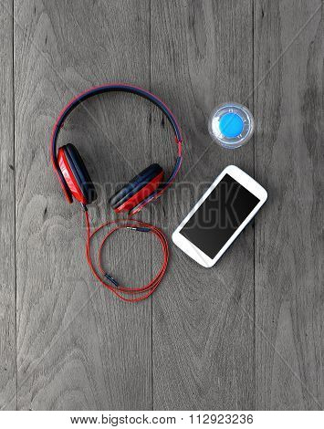 Bottle Of Water, Mobile Phone With Earphones On Wooden Table Background