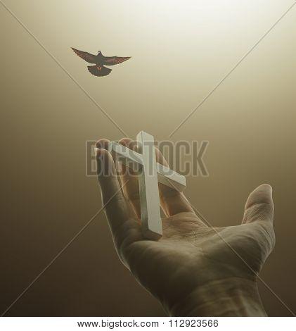 Hand holding white cross in dark light and bird on sky