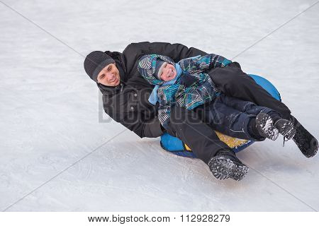 A Young Man With A Cheerful Boy With A Roller Coaster Ride In The Winter On The Ice.