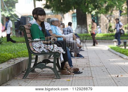 People resting on benches while walking around the bank of Hoan Kiem (Sword) lake