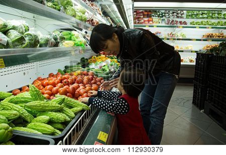 Asian people go shopping at a supermarket and choosing fresh fruit