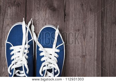 Youth blue sneakers with white untied the laces on wooden background