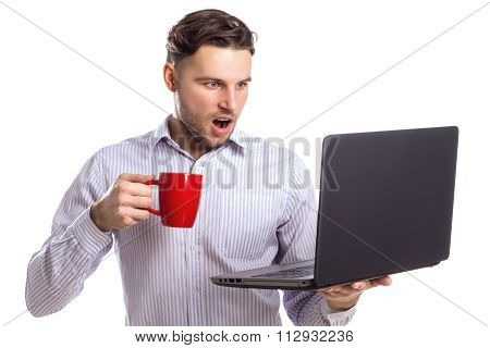 Handsome Angry Businessman Holding Red Cup And Looking At Laptop
