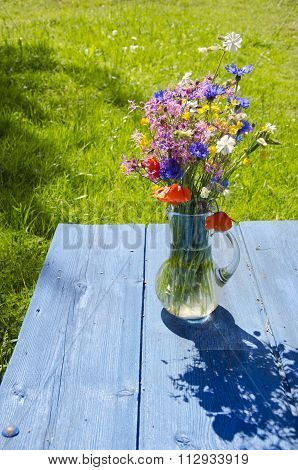 Wildfowers In Glass Jug On Blue Table