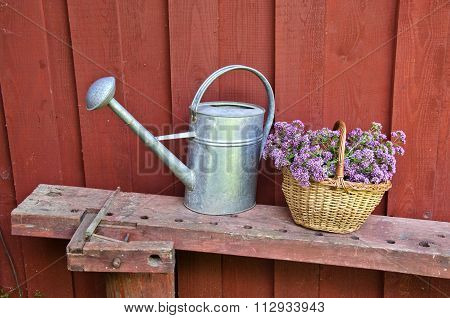 Metal Watering Can And Wicker Basket By The Wooden Wall