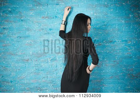 Beautiful Young Woman In A Black Dress Posing Against The Backdrop Of A Blue Brick Wall