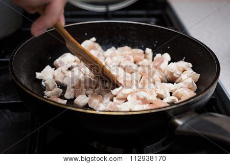 Frying cube sliced chicken meat in pan.
