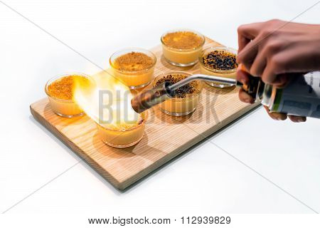 Woman's hands making creme brulee with gas-burner on wooden tray. Traditional French vanilla cream d