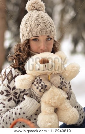 Beautiful, nice, smiling, little, attractive, wearing sweater, hut, mittens, girl with a fluffy, soft, beige, hite, teddy bear, cute toy, curly, light hair in snow, winter, frosty forest, sweet bear, tiny bear, petite