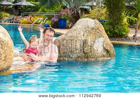 Active Father Teaching His Toddler Daughter To Swim In Pool On Tropical Resort. Summer Vacations And