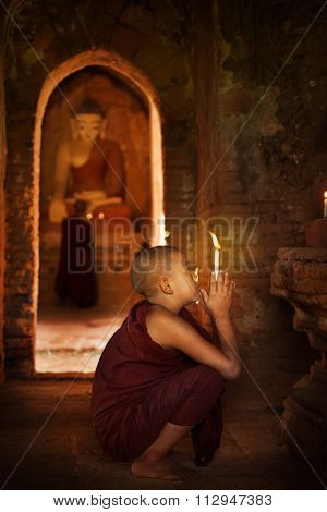 Portrait of young novice monks praying with candlelight inside a Buddhist temple, Bagan, Myanmar.