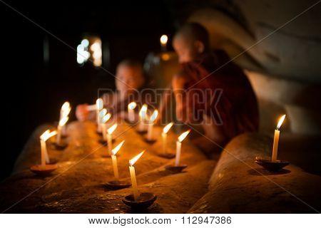 Little novice monks hand holding candlelight inside temple, Bagan, Myanmar.