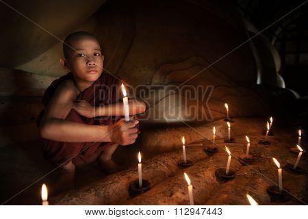 Little novice monk hand holding candlelight inside temple, Bagan, Myanmar.