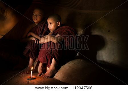 Young novice monks lighting up candle light inside a Buddhist temple, Bagan, Myanmar.
