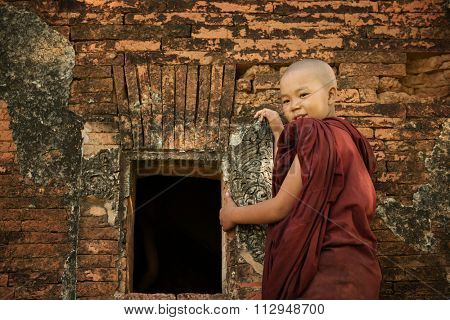 Young novice monk standing outside Buddhist temple, Bagan, Myanmar.