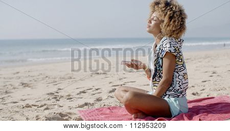 Young woman listening to music on headphones on the beach
