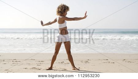 Slender fit young black woman warming up on the beach.