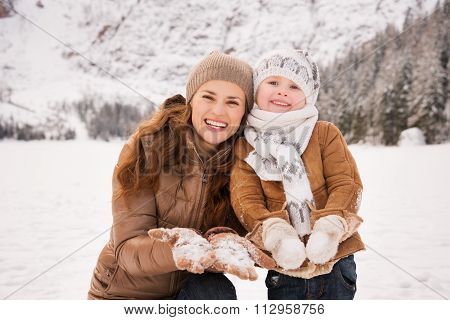 Mother And Child Showing Snowy Gloves In Winter Outdoors