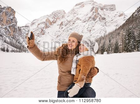 Happy Mother And Child Taking Photos In Winter Outdoors