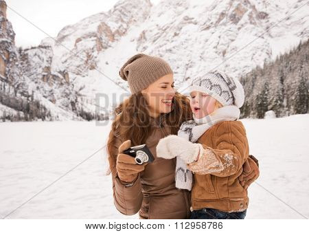 Happy Mother And Child With Photo Camera In Winter Outdoors