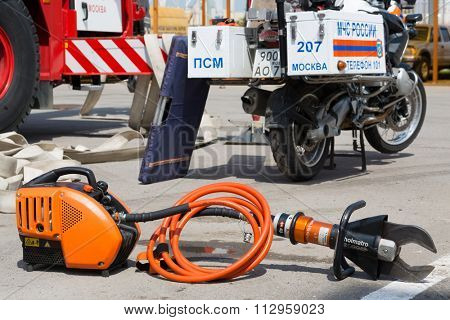 MOSCOW - MAY 29, 2015: Pneumatic clamp near red fire-engine and motorcycle with fire fighting equipmet