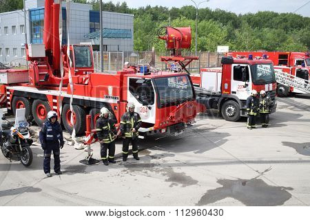 RUSSIA, MOSCOW - MAY 29, 2015: Fire trucks, fire engine with crane and motorcycles stand on territory of fire station.