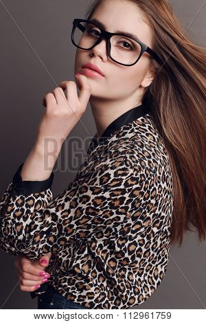 Woman With Dark Hair In Elegant Leopard Print Shirt And With Glasses