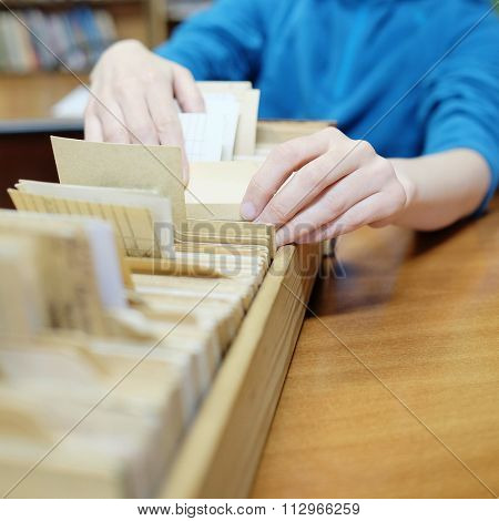 Librarian woman searches something in card catalog