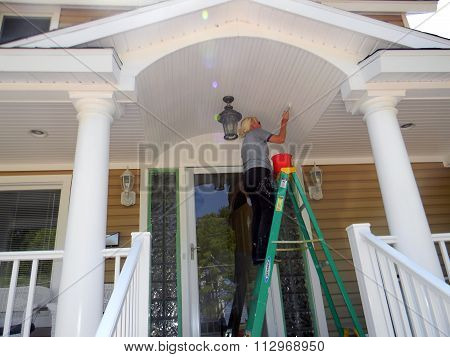 Painter Paints a Porch Ceiling