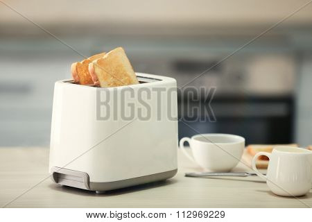 Toaster with dishes on a light kitchen table, close up