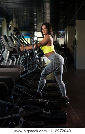 Latin Women On Elliptical Treadmill In Fitness Gym