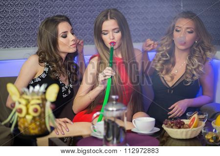 Beauty portrait of young three sexy women resting in the hookah room, focus on the left girl.