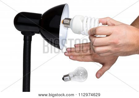Hand twists bulb in lighting