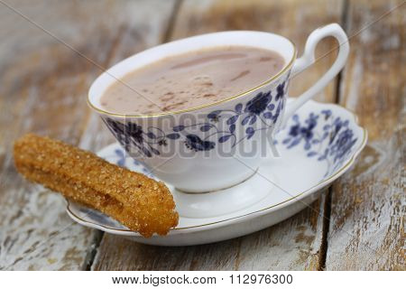 Spanish churro with cup of hot chocolate on rustic wooden surface