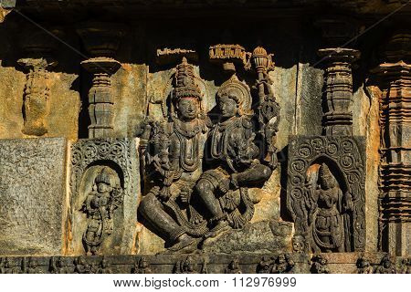 Artistic carvings of Lord Shiva with his concert Goddess Parvati on the walls of Hoysaleswara temple