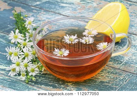 Cup of chamomile tea, fresh chamomile flowers and lemon on rustic wooden surface