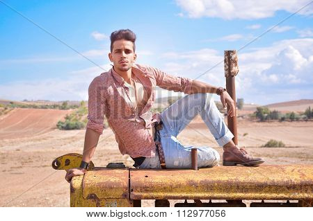 Attractive Fashion Farmer Sitting On Old Tractor.