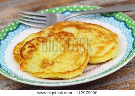 Crispy golden potato fritters on plate, closeup